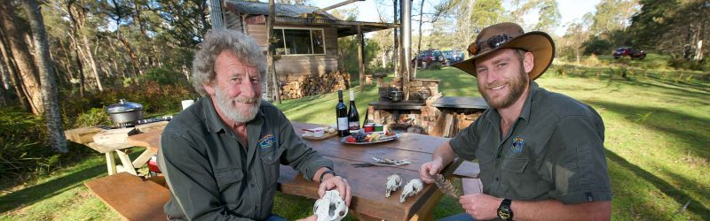 wildlife tours in tasmania - two guides talking about animals around a table with food and wine